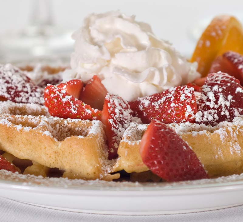 Waffle with Strawberries, whip cream and powered sugar