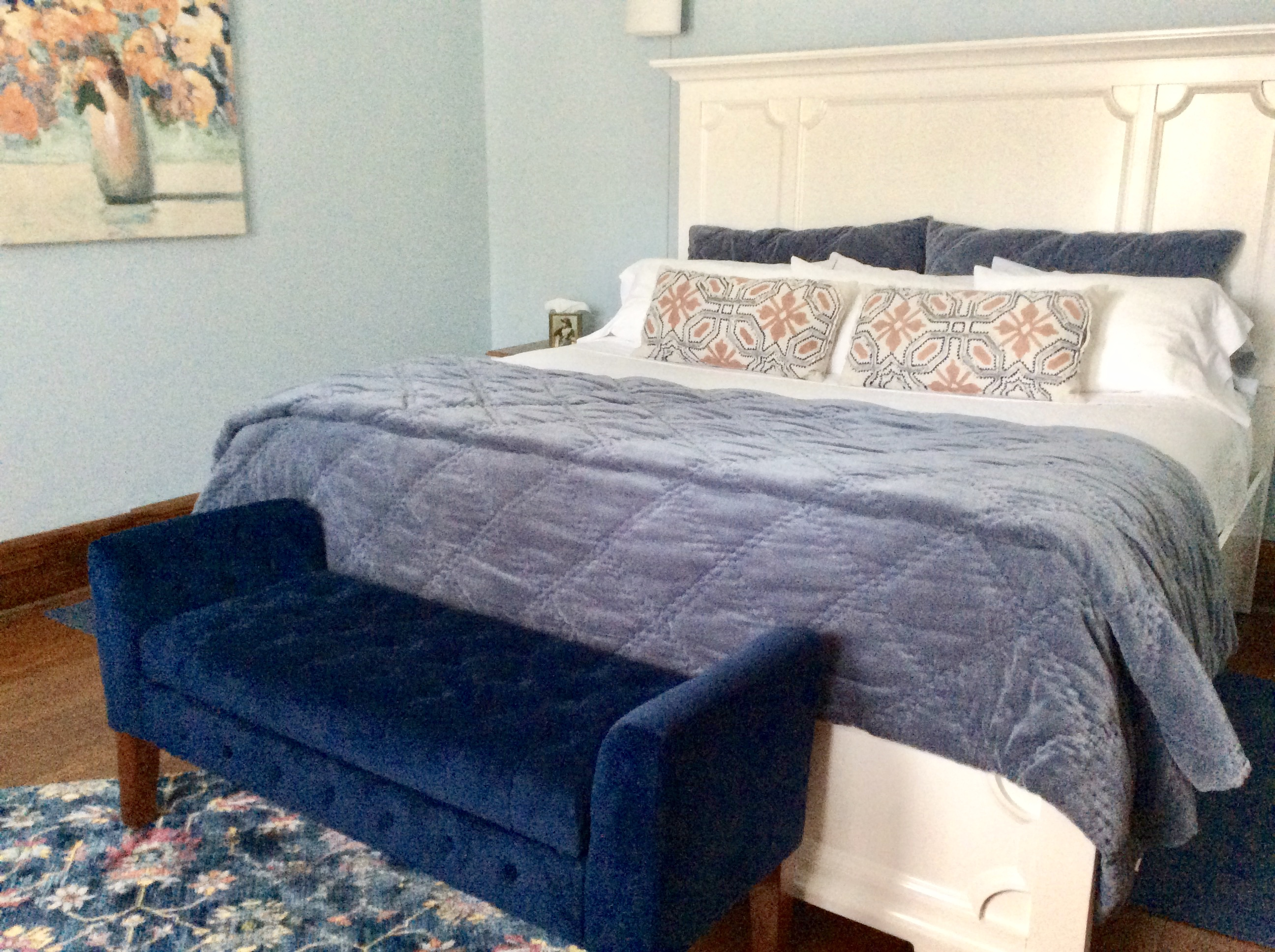King bed, stately white headboard.Navy blue and white and peach tones .